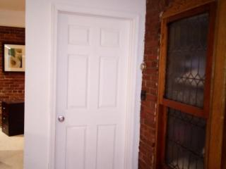 Door to 2nd bedroom which features brick-walls and futon (or bed) in bay windowbay window