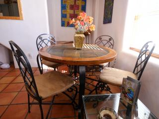 Dining room table for four people, plus counter with two bar stools